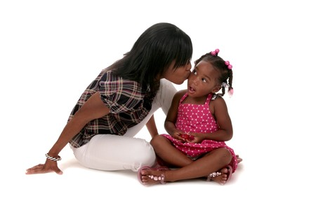 African American Mother Kissing Her Young Daughter on White Background photo