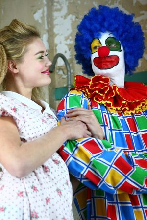 Clown Starring at a Beautiful Girl While She Smiles Adoringly at Him photo