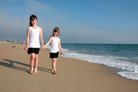 Happy Family of Sisters Holding Hands Walking Across the Beach Stock Photo - 4166453