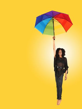 African Woman Falling While Holding an Umbrella on Yellow Background photo