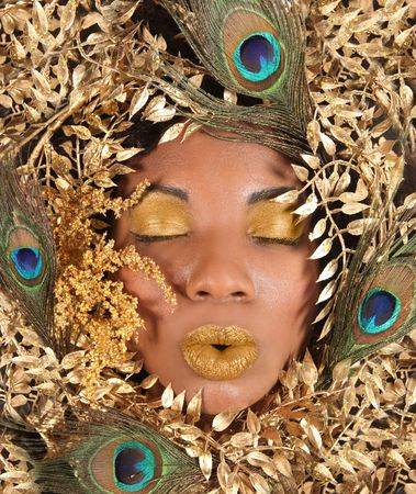 African American Woman Wrapped in Metallic Leaves and Peacock Feathers Stock Photo
