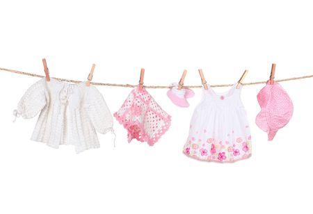 ropa colgada: Baby Girl ropa en un tendedero colgante aislados en el fondo blanco