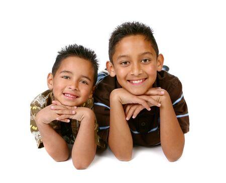 ヒスパニック系の若い兄弟が白の背景に笑みを浮かべて