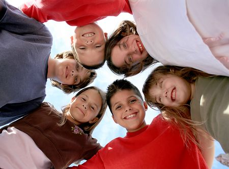 huddle: Happy Healthy Kids Hanging Out With Eachother Outdoors Stock Photo