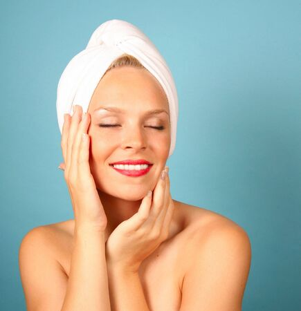 Woman With a Towel on Hair Awaiting Spa Treatment on Teal Background photo