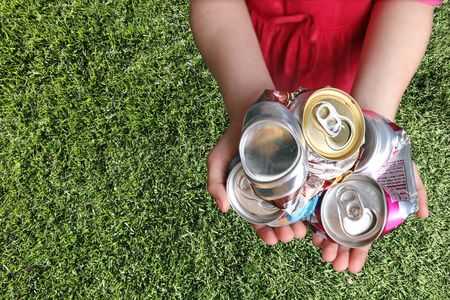 recycle waste: Latas de aluminio triturado para el reciclado en un Childs Manos