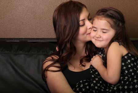 Mother Kissing Her Daughter on the Cheek photo