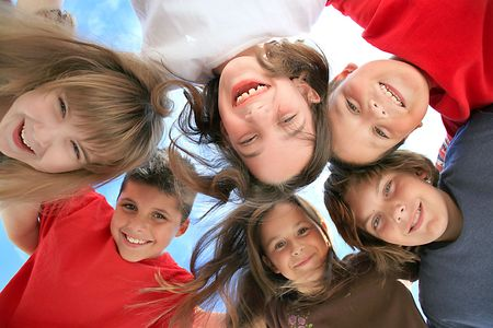 huddling: Happy Kids Huddling and Looking Down at the Viewer