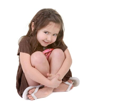 head tilted: Expressive Young Child Holding Her Legs With Head Tilted to the Side