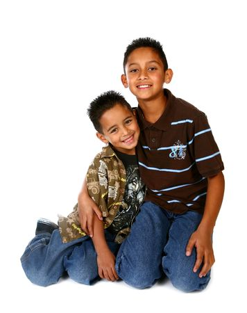 Hispanic Brothers Smiling and Hugging on White Background Imagens