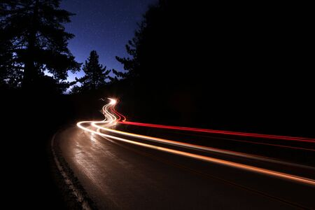 lifelike: Car Light Trails in the Mountains on a Starry Night Alongside the Highway. Noise is Present in the Sky Due to Shooting Conditions.