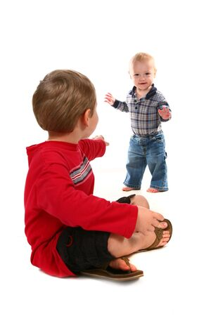 urging: Older Brother Urging Younger Child to Come to Him Stock Photo