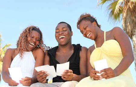 Three African American Friends Outdoors Looking at Photographs and Laughing photo