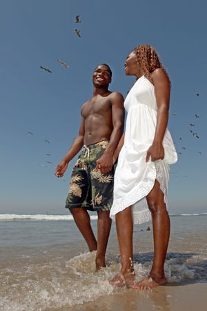 Beautiful Happy Black Couple Walking Along the Beach Holding Hands photo