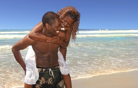 Couple in Love Playing on the Beach on the Ocean Water Stock Photo