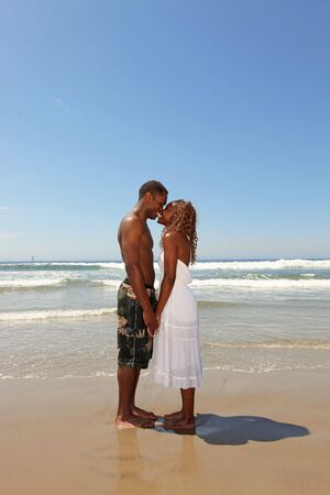 Happy African American Couple Kissing on the Beach in the Surf photo