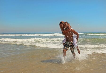 Happy African American Couple Splashing in the Ocean at the Beach photo