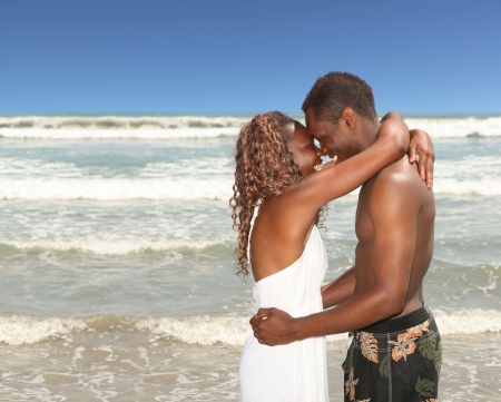 Loving Smiling Couple on the Beach With Arms Around Eachother photo