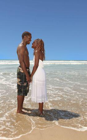 Happy Romantic Couple Holding Hands on the Beach photo