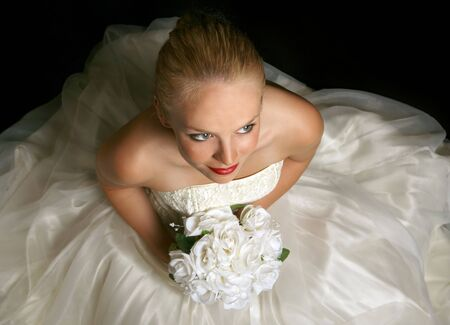 Beautiful Young Bride Sitting Holding Flowers photo