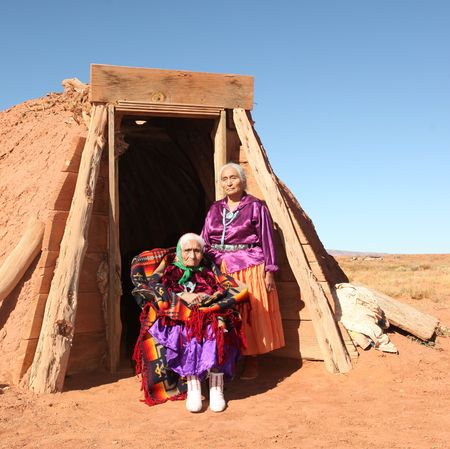 Elderly Native American women pose outside a tribal abode. They are full length viewable and looking at the camera. Squarely framed shot. Stock Photo - 5836543