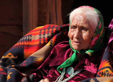 An elderly Native American woman sits among blankets. She is head and shoulders viewable and looking away from the camera. Horizontally framed shot.