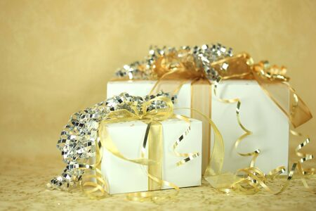 viewable: Closeup of two presents wrapped in gold and silver. No one is viewable in the image. Horizontally framed shot. Stock Photo