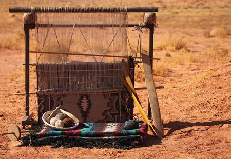 viewable: A blanket loom in the desert. No one is viewable. Horizontally framed shot.