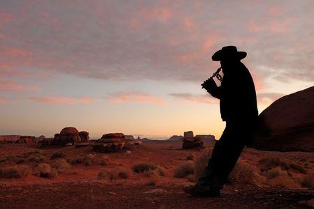 cappello cowboy: Maschio adulto met� indossare il cappello da cowboy e suonare il flauto. Egli � piena lunghezza visualizzabile, guardando lontano dalla fotocamera e silhouette. Foto incorniciate orizzontalmente.