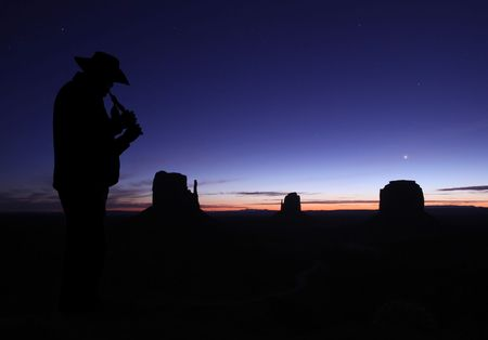 viewable: Mid adult male wearing cowboy hat and playing the flute. He is full length viewable, looking away from the camera and in silhouette. Horizontally framed shot.