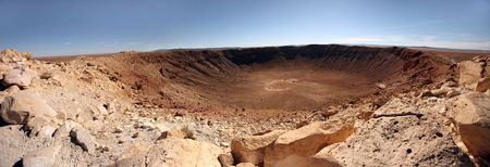 viewable: Panoramic view of desert landscape with crater. There is no one viewable in the image. Horizontally framed shot.
