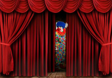 stage performer: A clown on stage behind a red curtain, looking away from the camera and full length viewable. Horizontally framed shot. Stock Photo