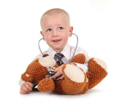 professions: Pretending Child Doctor Listening to a Teddy Bears Heartbeat  Stock Photo