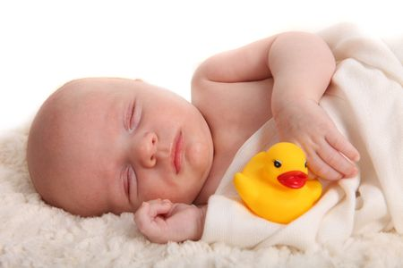 swaddled: Closeup of Sleeping Infant With a Rubber Duckie on White