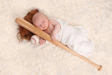swaddled: Swaddled Sleeping Baby Boy With a Baseball Bat and Ball Stock Photo