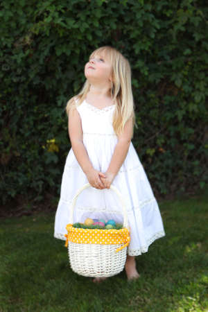 Sweet Little Girl Looking Up Holding Easter Basket with Eggs in a White Lace Dress photo