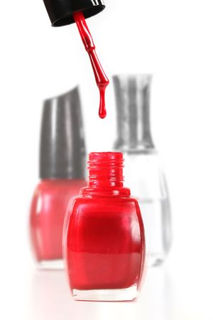 nail polish bottle: Finger Nail Polish Dripping Into a Bottle of Red Enamel Stock Photo