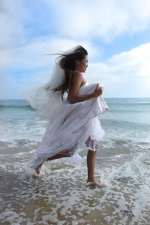Pretty Asian Bride Running Along the Beach in the Ocean Water photo