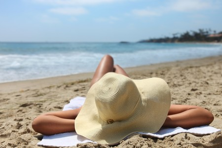 Beautiful Woman Laying Out Sunbathing at the Beach Wearing a Hat Stock Photo - 8059146