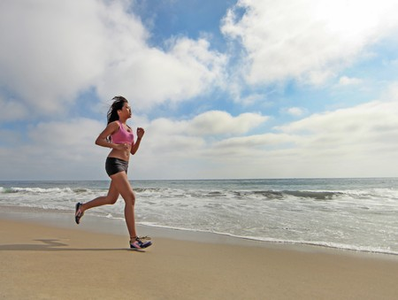 korean woman: Happy Female Runner Running at the Beach Jogging in the Sand