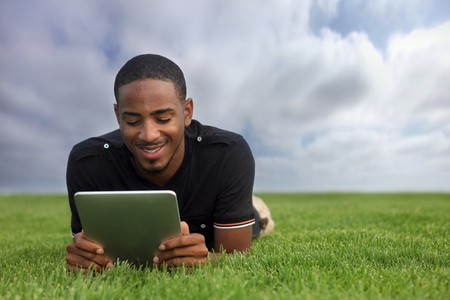 College Student Reading Outdoors Lying in the Grass photo