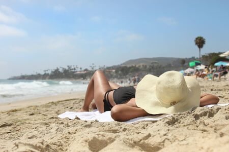 Beautiful woman sunbathing outdoors at the beach on a sunny day photo