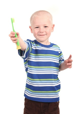 Small child brushing his teeth on a white background smiling and happy. photo