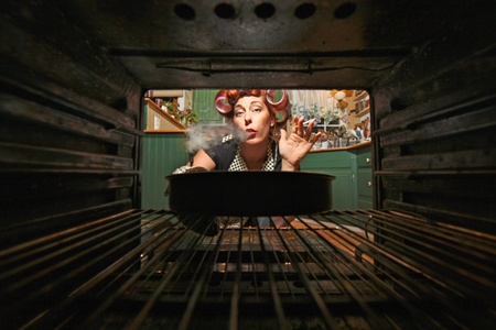 curlers: Housewife Smoking and Cooking Dinner in a Vintage Oven