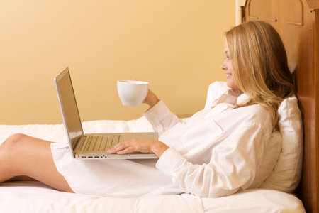 Smiling Happy Girl in Bed Using a Laptop Computer Stock Photo - 9863197