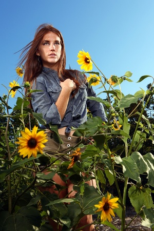 Beautiful Red Haired Woman Outdoors in a Sunflower Field photo