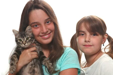 Sisters Holding Their Young Kitten on White Stock Photo - 11227125