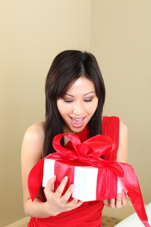 Asian Woman Holding a Gift Package Wrapped With Ribbon photo