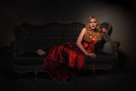 Elegant Young Lady in Red Dress and Dramatic Lighting Banco de Imagens