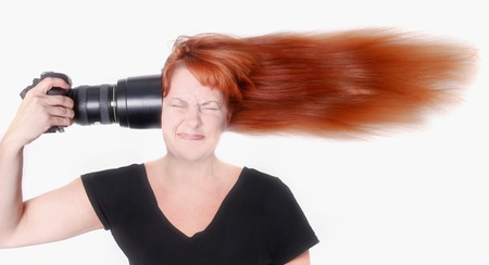 Female Photographer With Camera Pointed at Her Head photo